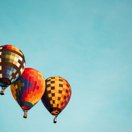 three flying hot air balloons