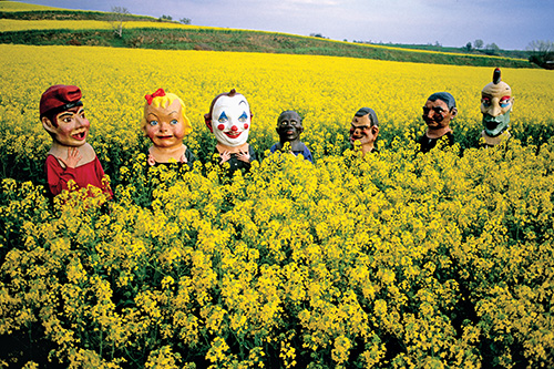 Photo by Tino Soriano | Lake Banyoles, Catalonia, Spain | 2005 | Masked people cross a mustard field on the way to a summer festival.