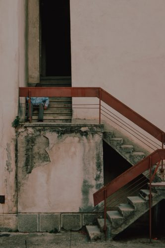 man in blue shirt sitting on concrete stairs